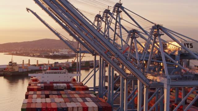 drone flight around cargo ship and cargo cranes with logistics yard in background - kran stock-videos und b-roll-filmmaterial