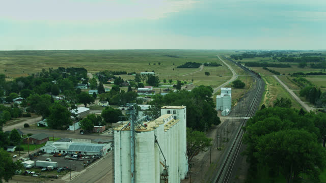 drone flight around grain elevator as freight train passes through town - freight elevator stock videos & royalty-free footage