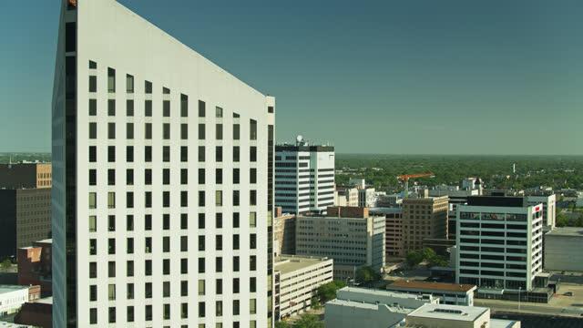 stockvideo's en b-roll-footage met dronevlucht rond modern kantoorgebouw in het centrum van wichita - sunny