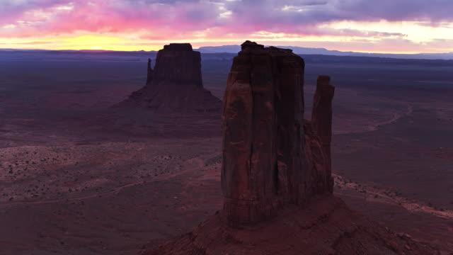 vídeos de stock, filmes e b-roll de vôo do zangão em torno do vale do monumento mitten buttes no nascer do sol - mitten