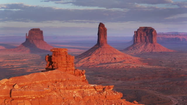 drone flight around monument valley outcrop with buttes in distance - utah stock videos & royalty-free footage