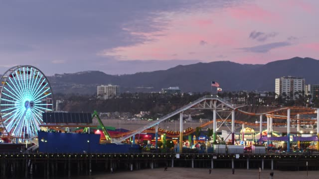 drone flight around santa monica pier at dusk - santa monica pier stock videos & royalty-free footage