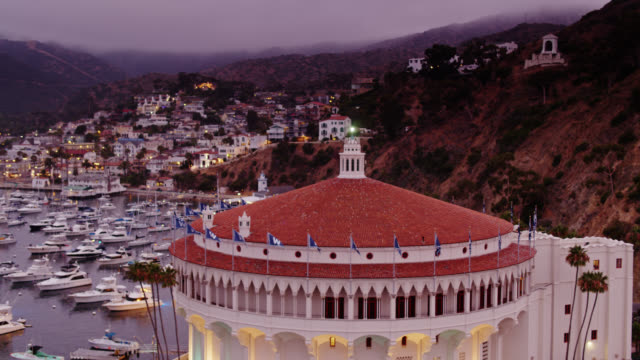 drone flight around tiled roof of catalina casino with avalon lit up behind - channel islands california stock videos & royalty-free footage
