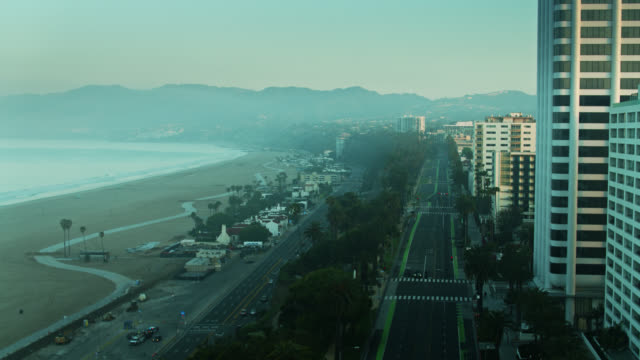 drone flight away from pch and ocean avenue on quiet foggy morning in santa monica during covid-19 lockdown - ocean avenue stock videos & royalty-free footage