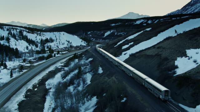 drone flight behind passenger train in snowy mountains - locomotive stock videos & royalty-free footage