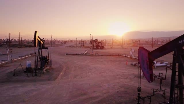 drone flight between pumpjacks in midway-sunset oil field, kern county, california - trivella petrolifera video stock e b–roll