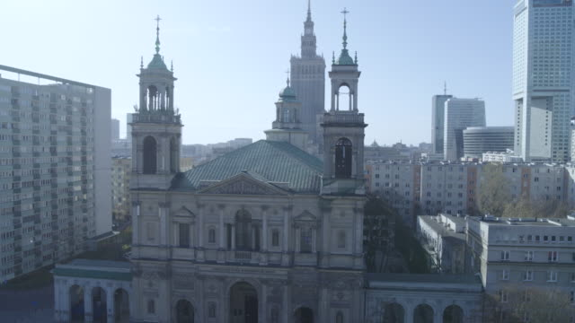 drone flight of a deserted plac grzybowski with a view of the church kosciol pw. wszystkich swietych in daytime in downtown warsaw during the corona... - aprile video stock e b–roll
