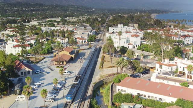 drone flight over amtrak pacific surfliner in santa barbara station - サンタバーバラ点の映像素材/bロール