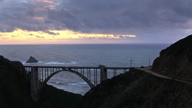 drone flight over bixby bridge at sunset - bixby creek bridge stock videos & royalty-free footage