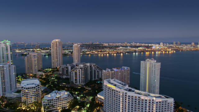 drone flight over brickell key looking towards port of miami and fisher island at twilight - miami stock videos & royalty-free footage