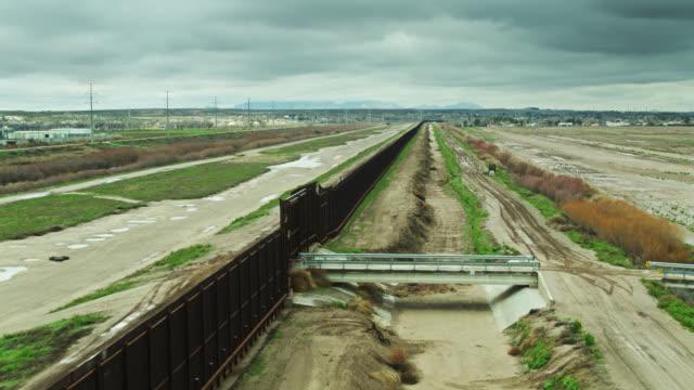 vidéos et rushes de drone flight over bridge crossing ditch to gate in u.s.-mexico border wall - texas