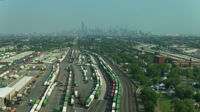 vídeos de stock, filmes e b-roll de voo de drone sobre terminal de carga movimentadopara frente ao skyline de chicago - chicago illinois