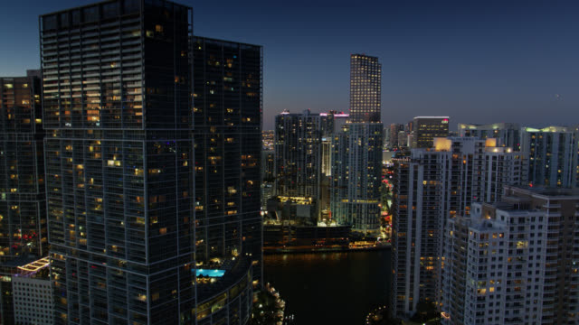vidéos et rushes de drone flight over channel separating brickell key from miami mainland at nightfall - miami