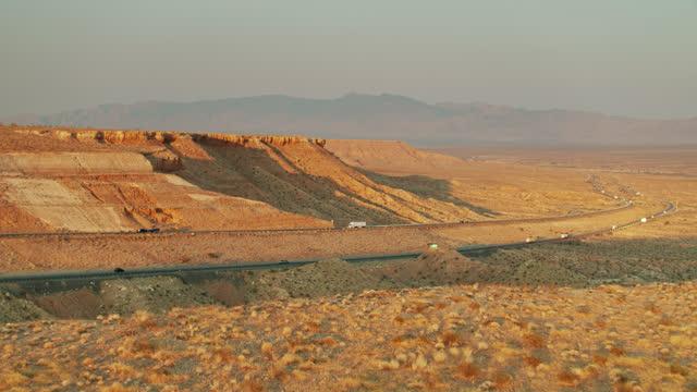 stockvideo's en b-roll-footage met drone flight over cliff edge in desert revealing i-15 - nevada