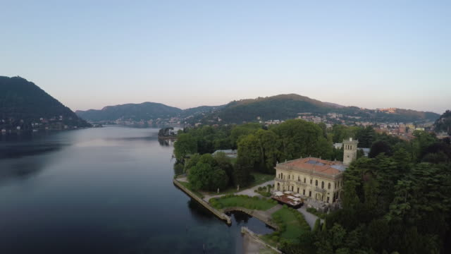 Drone flight over Como lake and a castle with a swimming pool at sunrise, wide angle lens, pedestal movement