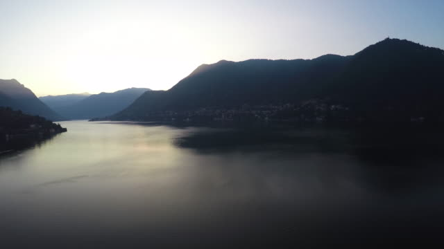 Drone flight over Como lake at sunrise with a wide angle lens, pan left movement
