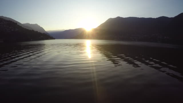 Drone flight over Como lake at sunrise with a wide angle lens, pedestal movement