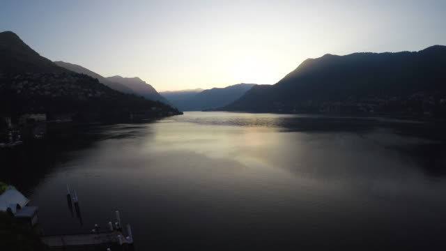 Drone flight over Como lake, the Italian flag and a pier at sunrise with a wide angle lens, pedestal movement