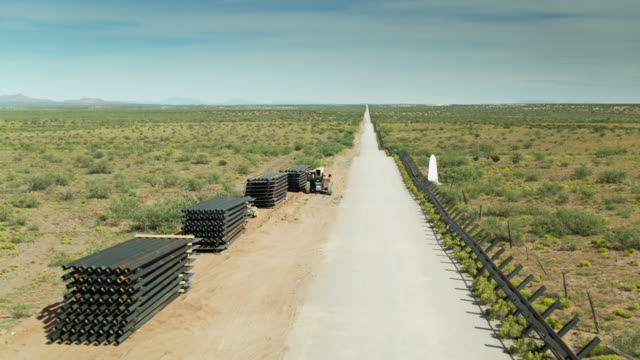 drone flight over construction materials at us-mexico border - vanishing point stock videos & royalty-free footage