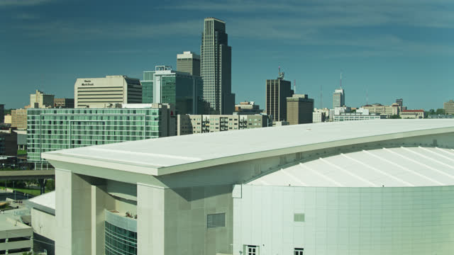 drone flight over convention center towards downtown omaha - auditorium stock videos & royalty-free footage