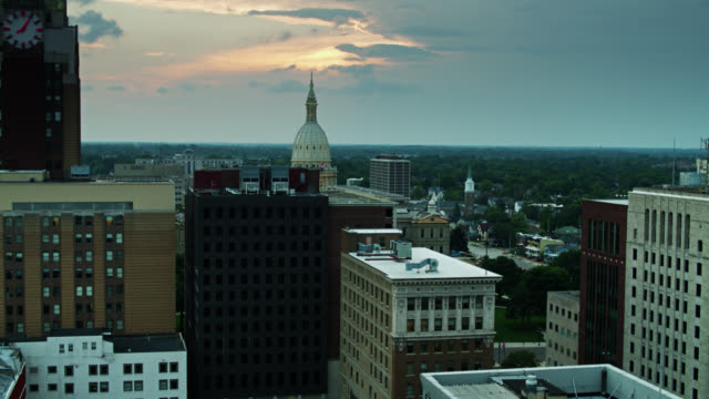 drone flight over downtown lansing rooftops towards michigan state capitol building - lansing stock videos & royalty-free footage