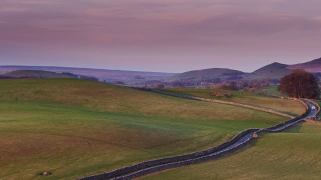 Drone Flight Over Fields and Lane in Yorkshire Dales at Sunset
