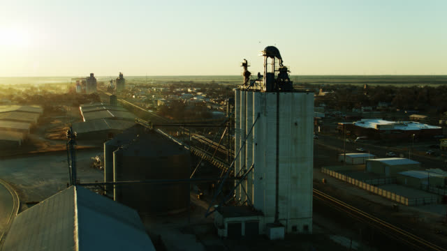 drone flight over grain silo, train tracks and main street of muleshoe, texas at sunrise - prairie stock videos & royalty-free footage