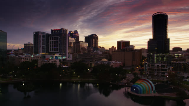 drone flight over lake eola past eola park and downtown buildings in orlando at sunset - abenddämmerung stock-videos und b-roll-filmmaterial