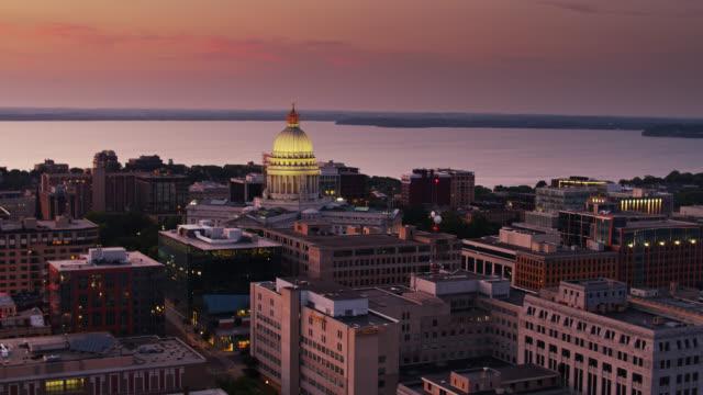 ウィスコンシン州議会議事堂に向かって日没時にマディソンの屋上の上にドローン飛行 - ウィスコンシン州点の映像素材/bロール