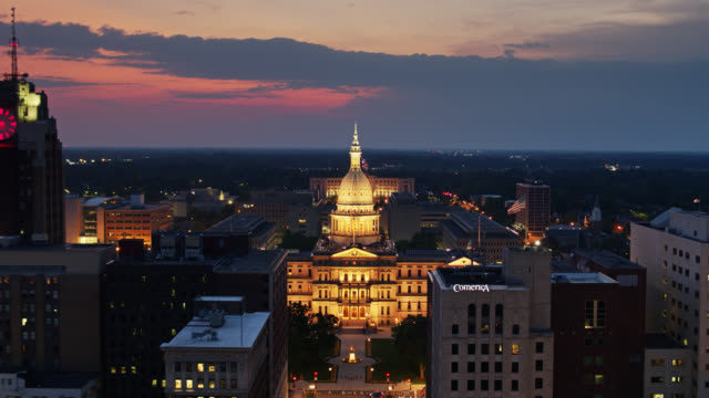 drone flight over michigan avenue towards state capitol dome lit up at night - lansing stock videos & royalty-free footage