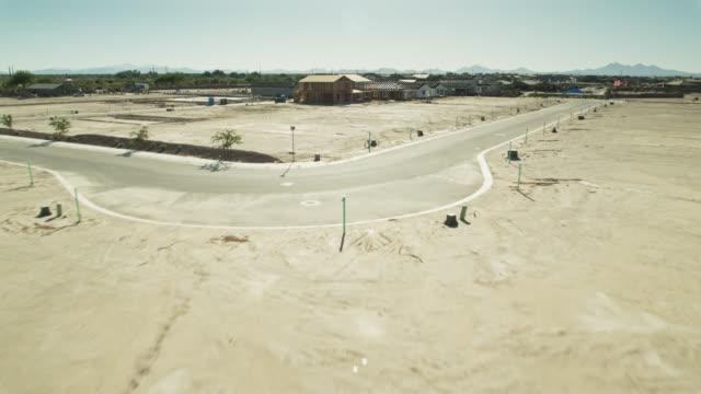 drone flight over newly graded land towards growing suburban development in arizona - development stock videos & royalty-free footage