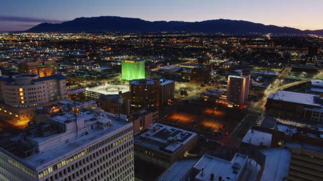 drone flight over office buildings and hotels in downtown albuquerque before sunrise - albuquerque new mexico stock videos & royalty-free footage