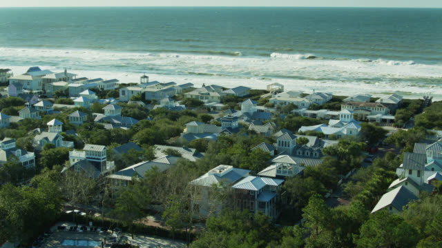 drone flight over pastel colored vacation homes in seaside, florida - gulf of mexico stock videos & royalty-free footage