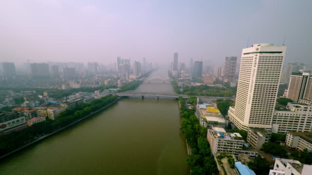 drone flight over pearl river with guangzhou skyline at daytime - spoonfilm stock-videos und b-roll-filmmaterial