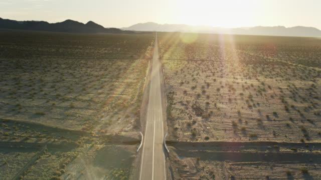 vidéos et rushes de vol de drone au-dessus de la route 66 dans le désert de mojave au lever de soleil - route 66