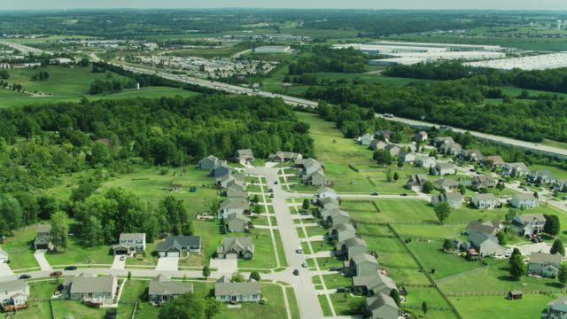 vidéos et rushes de drone flight over suburban homes and distribution centers on either side of i-75 in ohio - uniformité