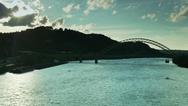 vidéos et rushes de vol de drone au-dessus de la rivière de l'ohio vers le pont de west end au coucher du soleil - rivière ohio