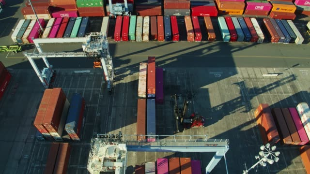 drone flight over top handler and straddle carrier moving shipping containers in port of long beach - straddle carrier stock videos & royalty-free footage