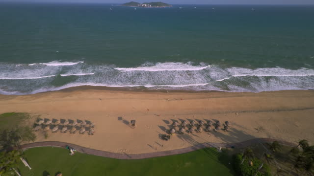 drone flight over tourist resort in yalong bay towards the south cina sea in sanya, hainan province, china. - spoonfilm stock-videos und b-roll-filmmaterial