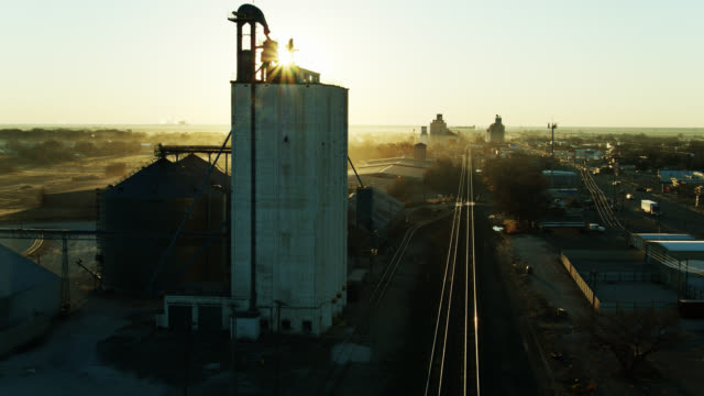 drone flight over train tracks running through small town in texas at sunrise - prairie stock videos & royalty-free footage