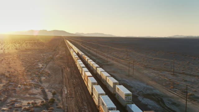 vídeos de stock e filmes b-roll de drone flight over two passing freight trains - transportation