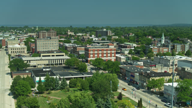 drone flight over veteran's park and downtown buildings in fond du lac, wisconsin - street name sign stock videos & royalty-free footage