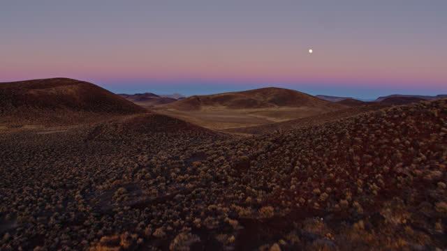 drone flight over volcanic desert in lunar crater national natural landmark at twilight - natural landmark stock videos & royalty-free footage