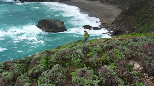 drone flight over woman walking along ridge in big sur - northern california stock videos & royalty-free footage