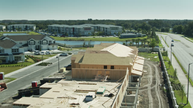 drone flight over wood frame of half built suburban homes - mittelschicht stereotypen stock-videos und b-roll-filmmaterial