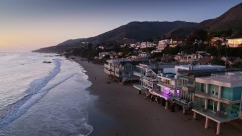 stockvideo's en b-roll-footage met drone vlucht verleden beachfront huizen op lechuza point in malibu, californië - klif