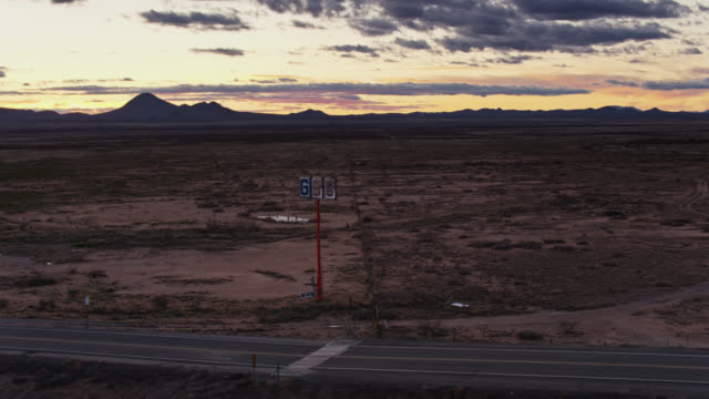 drone flight past broken gas station sign in desert - interstate 10 stock videos & royalty-free footage