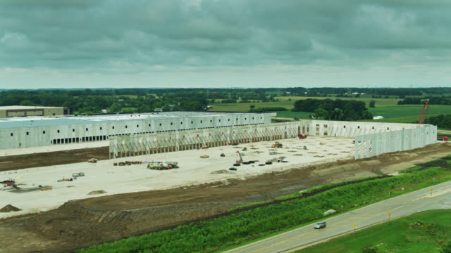 drone flight past distribution center being built on wisconsin farmland - construction vehicle stock videos & royalty-free footage
