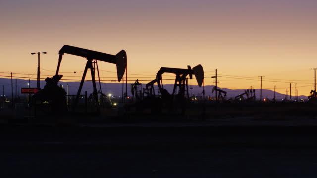 vídeos de stock, filmes e b-roll de voo do zangão passou a acenar burro bomba jacks silhueta por do sol - poço de petróleo