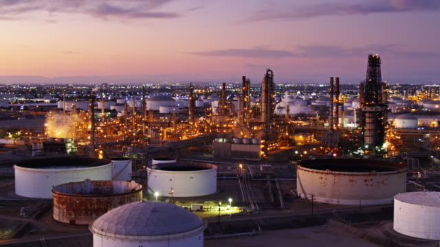 drone flight past oil refinery with la sprawl beyond - oil refinery stock videos & royalty-free footage